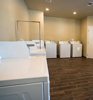 What a spacious laundry room with 4 washers and 4 dryers, an adjacent bath house/restroom.